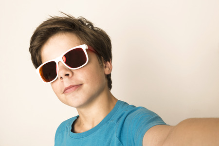 happy teenagers: Happy young boy with sunglasses take a selfie with a smartphone at home isolated on white background