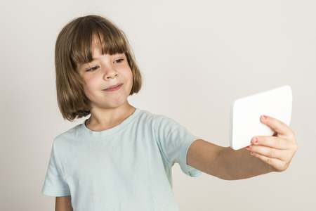girl with camera: Happy little girl take a selfie with a smartphone at home isolated on white background