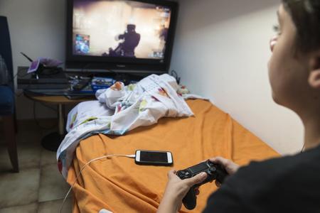 jugando videojuegos: Ni�o jugando videojuegos sentado en la cama en su habitaci�n mientras se carga el tel�fono Foto de archivo