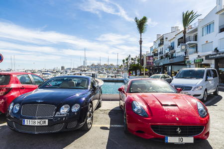 Puerto Banus, Spain - August 15, 2015: Red Ferrari and other sport cars parked next to luxurious yachts moored in Puerto Banus, a marina near Marbella, Andalusia, Spain