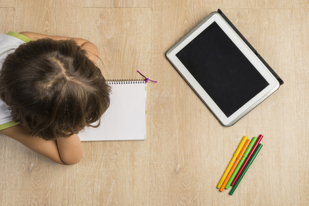 Little girl doing homework lying on the floor with a notebook and a digital tablet