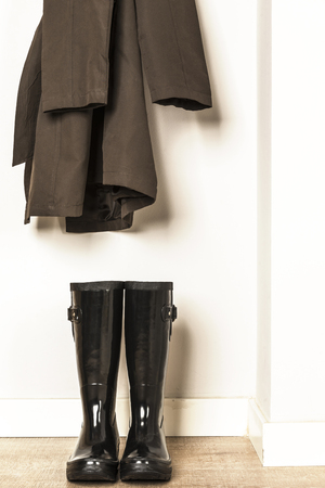 forecaster: Raincoat and black wellies water ready for use in a rainy day Stock Photo