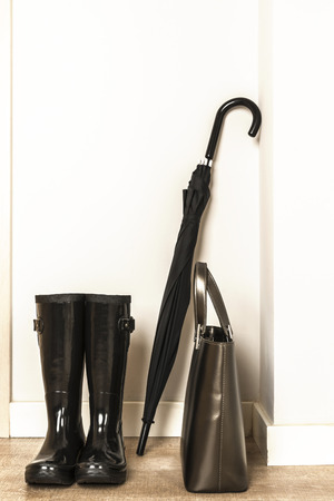 wellies: Black wellies, umbrella and bag ready for use in a rainy day