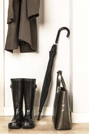 forecaster: Raincoat, wellies, umbrella and bag ready for use in a rainy day Stock Photo