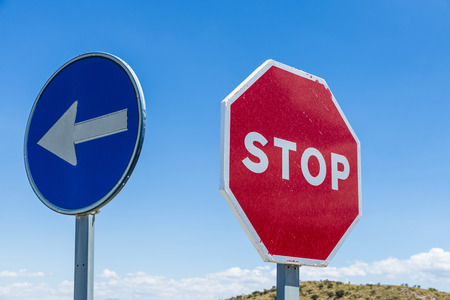 compulsory: Stop sign and signal direction compulsory against the sky in Spain