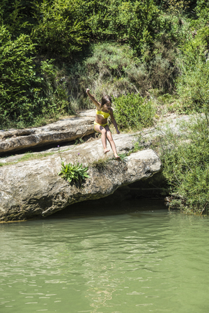 happy little girl: Little girl jumping in a river in Catalonia, Spain