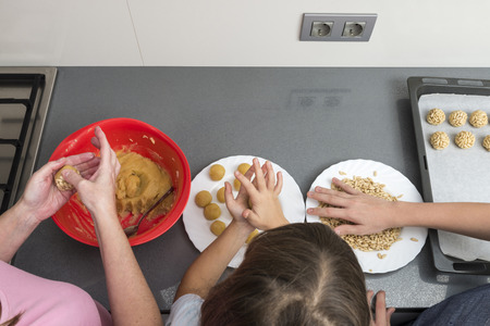 Family kneading marzipan for make panellets in the kitchen. Panellet are traditional desserts of All Saints holiday, known as Castanyada in Catalonia, Spain