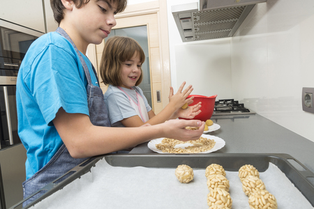 make known: Little girl and young boy kneading marzipan for make panellets  in the kitchen. Panellet are traditional desserts of All Saints holiday, known as Castanyada in Catalonia, Spain