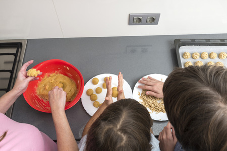 panellets: Family kneading marzipan for make panellets in the kitchen. Panellet are traditional desserts of All Saints holiday, known as Castanyada in Catalonia, Spain