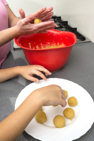 panellets: Mother and daughter kneading marzipan for make panellets  in the kitchen. Panellet are traditional desserts of All Saints holiday, known as Castanyada in Catalonia, Spain
