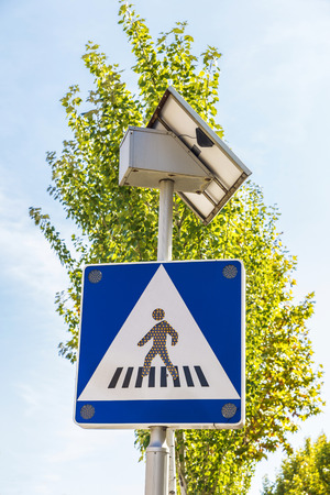 cross street with care: Crosswalk signal that is powered by solar energy with its own solar panel
