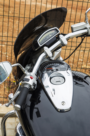 rearview: Closeup of chrome black motorcycle parked. In the rearview mirror the Agbar tower looks Stock Photo