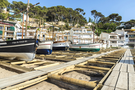 ingenious: Girona, Spain - July 1, 2015: Typical fishing boats on the beach of Sa Riera in the Costa Brava, Catalonia, Spain. The boats are parked on the sand by an ingenious system of rails