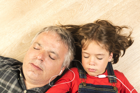 happy little girl: Father and daughter listening to music together with headphones stretched on a wooden floor at home