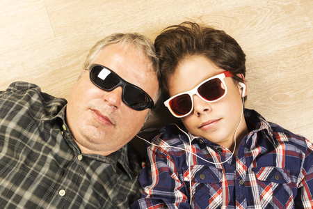12 13: Father and son listening to music together with headphones and sunglasses stretched on a wooden floor at home