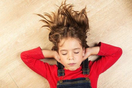 stretched: Smiling little girl stretched on a wooden floor with his hands behind his head and eyes closed Stock Photo