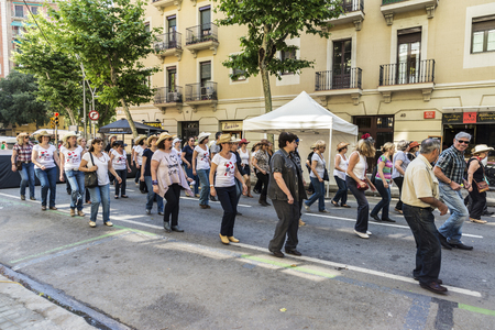 Barcelona, Spain - June 6, 2015: Adult people dancing country in the streets of Barcelona during the holidays Editorial
