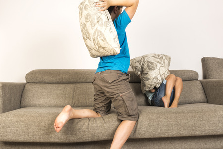 peleando: Los niños que luchan junto con las almohadillas en el sofá en casa Foto de archivo
