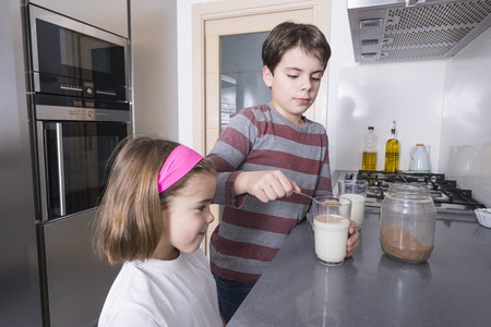 brother: Children getting ready a glass of chocolate milk
