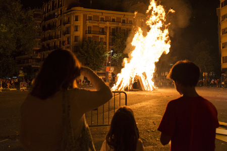 Family looking at a bonfire at night to celebrate the festivity of Sant Joan on a street in Barcelona, Catalonia, Spain
