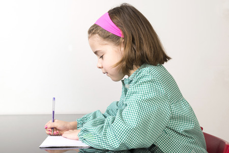smock: Little girl with a green plaid smock writing in a notebook at home
