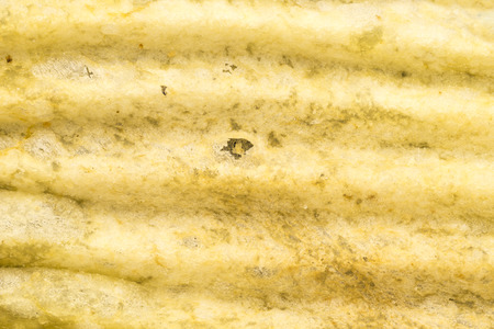 full of holes: Close-up of ribbed potato snack
