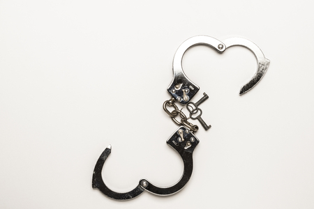 snitches: Close-up of a silver handcuffs with key in heart shape on white background