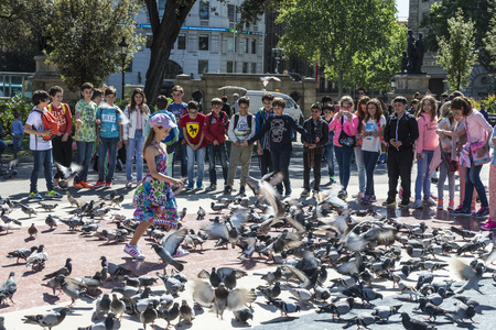 scare: Barcelona, Spain - May 4, 2016: School children playing to scare away pigeons in Placa Catalunya
