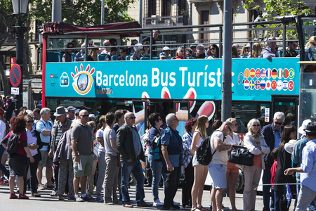 tourists stop: Barcelona, Spain - May 4, 2016: Many tourists waiting at the bus stop tourist