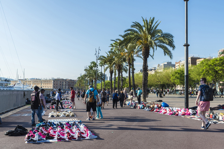 Barcelona, Spain - June 1, 2016: Flea market in the port Vell. This market consists of immigrants and it is illegal because fakes are sold. Editorial