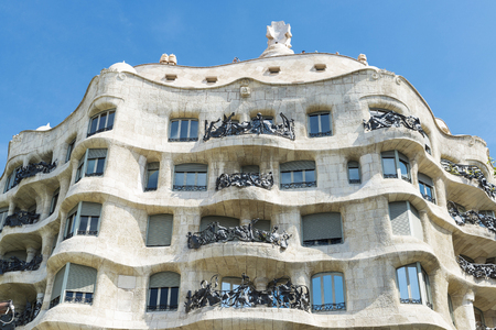 modernist: Barcelona, Spain - May 25, 2016: View of Casa Mila, better known as La Pedrera, designed by Antoni Gaudi, and a modernist style streetlight on the Passeig de Gracia, Barcelona, Catalonia, Spain. Editorial