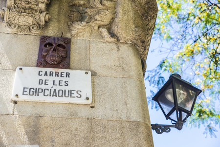 hideous: Street name decorated with a skull and hideous faces with a classic black lamppost in Barcelona, Catalonia, Spain