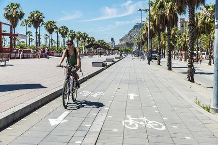 moll: Barcelona, Spain - June 21, 2016: People walking and girl cycling on the promenade called Moll de la Fusta in Barcelona, Catalonia, Spain Editorial