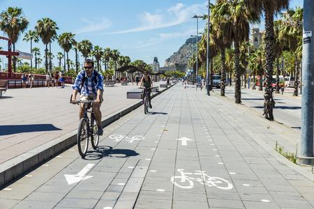 moll: Barcelona, Spain - June 21, 2016: People walking and cycling on the promenade called Moll de la Fusta in Barcelona, Catalonia, Spain