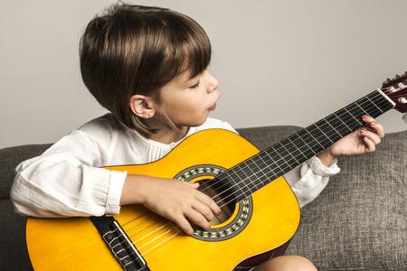 uñas pintadas: Niña tocando la guitarra sentado en el sofá de casa