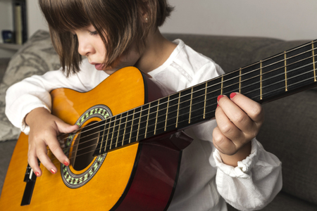 girl playing guitar: Little girl playing guitar sitting on the sofa at home