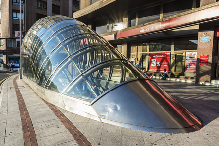 subway entrance: Bilbao, Spain - August 13, 2016: Modern subway entrance formed by a curved metal and glass structure and people walking