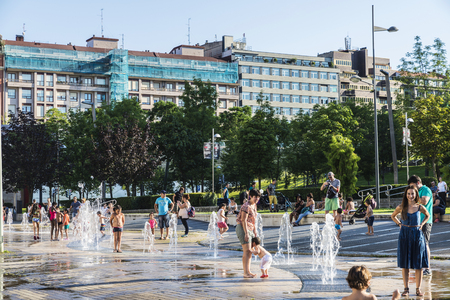 Bilbao, Spain - August 13, 2016: Children bathing in a park with fountains and water jets in the center of Bilbao