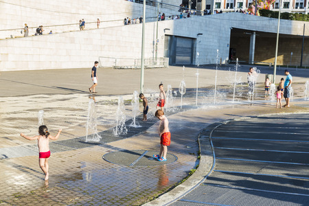 jets: Bilbao, Spain - August 13, 2016: Children bathing in a park with fountains and water jets in the center of Bilbao
