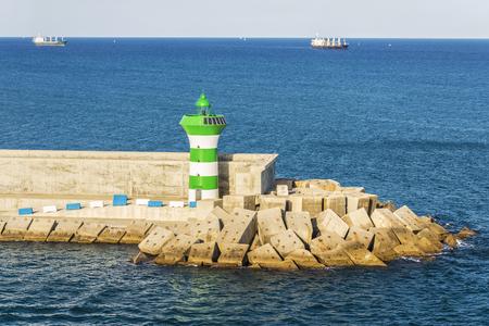 Vuurtoren op een golfbreker met twee tankers die op de achtergrond in de haven van Barcelona in Catalonië, Spanje varen