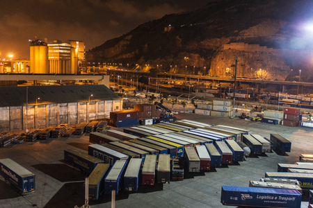 Barcelona, Spain - August 19, 2016: Containers waiting to be shipped at night in the port of Barcelona in Catalonia, Spain