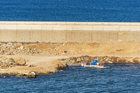 Barcelona, Spain - August 27, 2016: Worker in a boat repairing a breakwater in the port of Barcelona in Catalonia, Spain