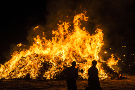 People celebrate St Johns Eve (Sant Joan) around a bonfire in a beach of Estartit, Costa Brava, Catalonia, Spain. St Johns eve celebration around a bonfire is reminiscent of Midsummers pagan rituals.
