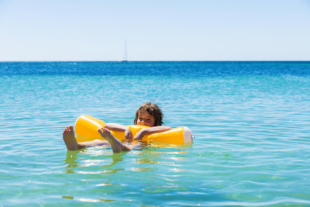 bather: Little girl bathing with a float on the beach in summer in Alghero, Sardinia, Italy