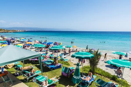 bather: Alghero, Italy - August 22, 2016: Beach full of bathers in summer in Alghero, Sardinia, Italy