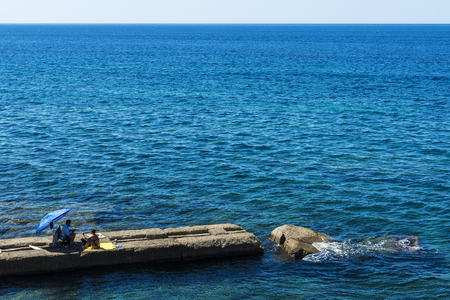 bather: Alghero, Italy - August 26, 2016: A man and a woman sitting on a stone wall on the sea in the old historic town of Alghero in Sardinia, Italy