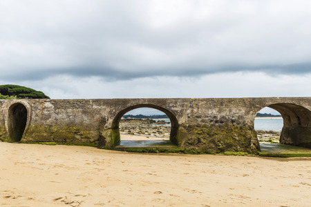 shorelines: Old stone bridge on El Sardinero beach in Santander, Spain Stock Photo