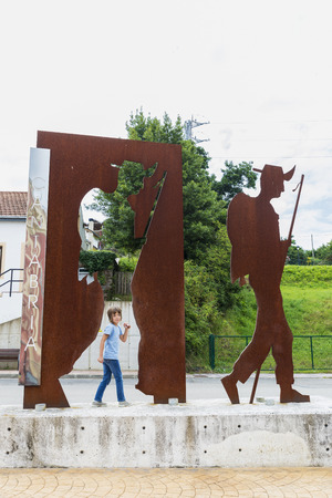 Cantabria, Spain - August 11, 2016: Monument of the camino de Santiago where a girl imitates the pose of the figure in Cantabria, Spain  Stock Photo