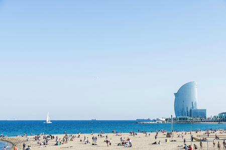 bather: Barcelona, Spain - June 1, 2016: Barcelona beach full of people and bathers with W hotel in the background Editorial