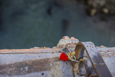 tied in: Red heart shaped padlock tied together with other padlocks on a bridge in Rome, Italy
